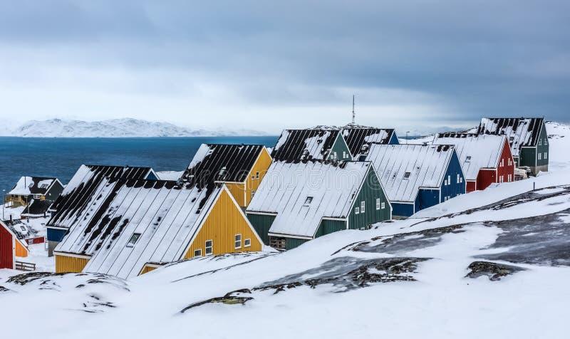 在雪盖的黄色,蓝色,红色和绿色因纽特人房子在努克市,格陵兰海湾  免版税库存图片