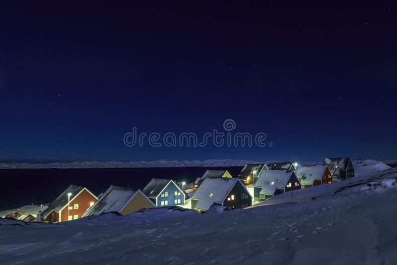 在雪盖的黄色,蓝色,红色和绿色因纽特人房子在海湾在星光天空下,努克市,格陵兰 库存图片