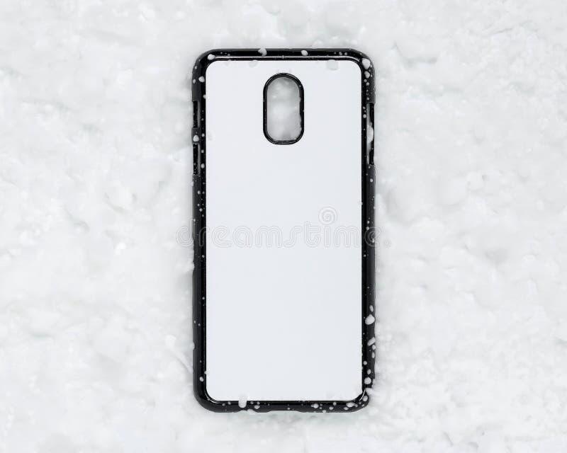 在雪纹理背景的黑流动盖子 电话盒和白色表面打印的 免版税库存照片