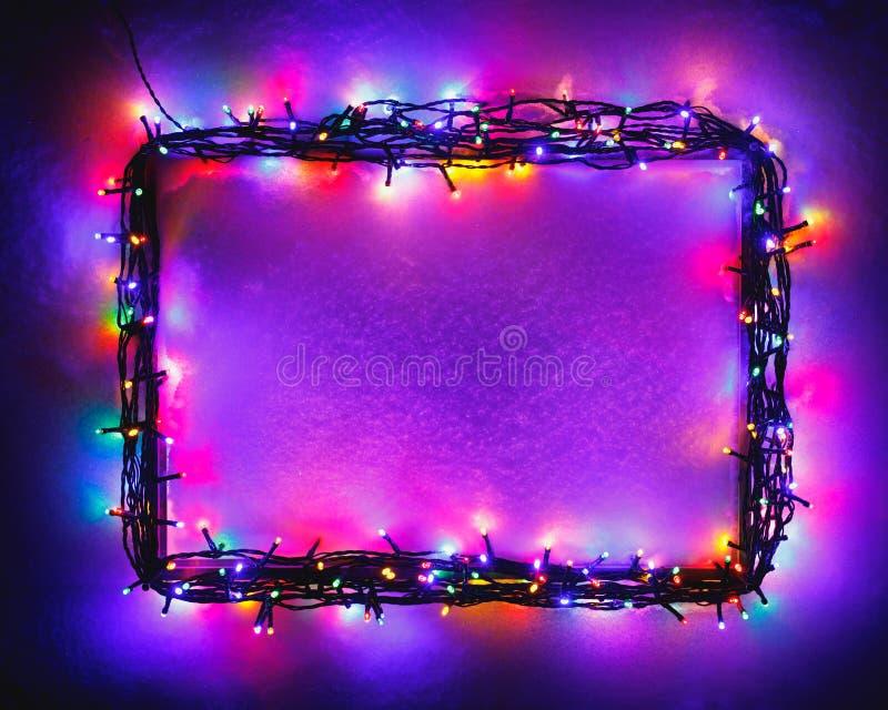 在雪背景,紫色颜色的圣诞灯框架 免版税库存图片