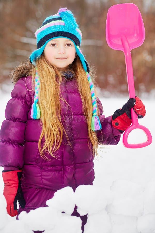 在雪障碍后站立小女孩的画象  免版税库存照片