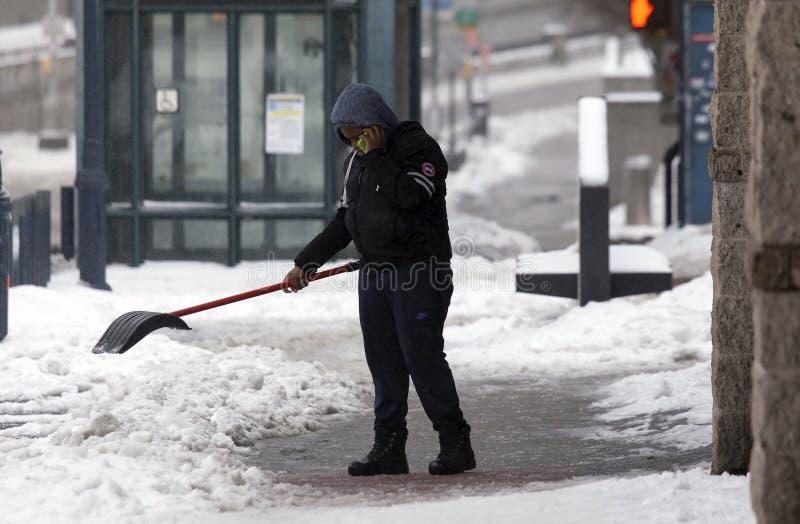 在雪风暴期间,人使用铁锹的和cel打电话 图库摄影