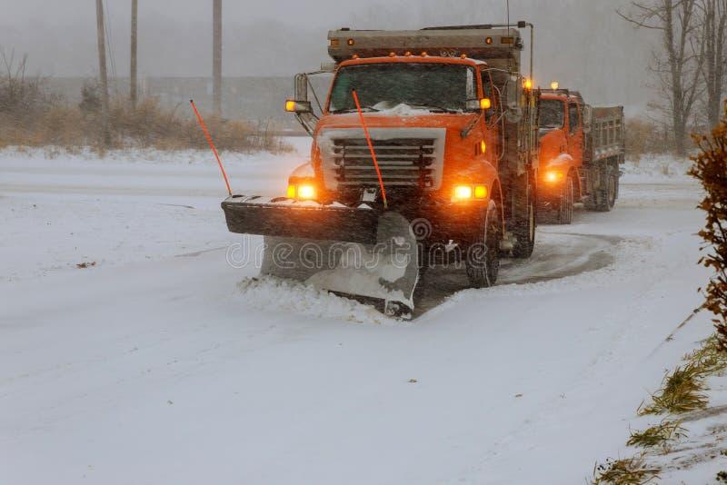 在雪飞雪期间的大拖拉机撤除雪街道 库存图片