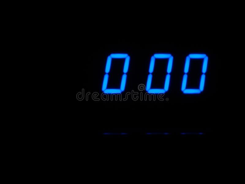 在零,蓝色图的数字读秒在黑blackground 定时器,分钟 免版税图库摄影