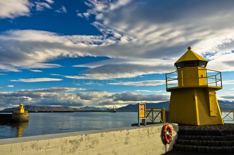在雷克雅未克港口入口的黄色灯塔清早 库存照片