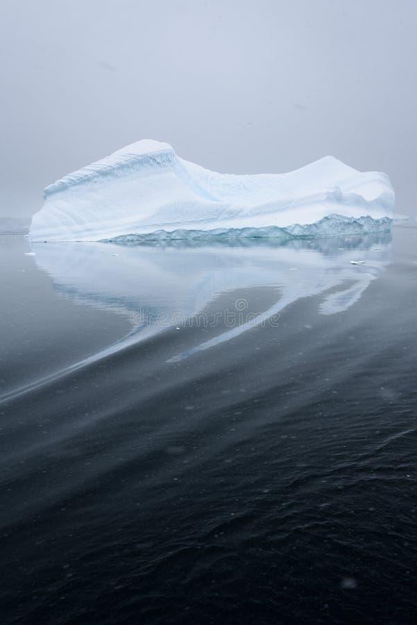 在雾和漂浮覆盖的雕刻的冰山在南极洲的黑暗的水域中 库存图片