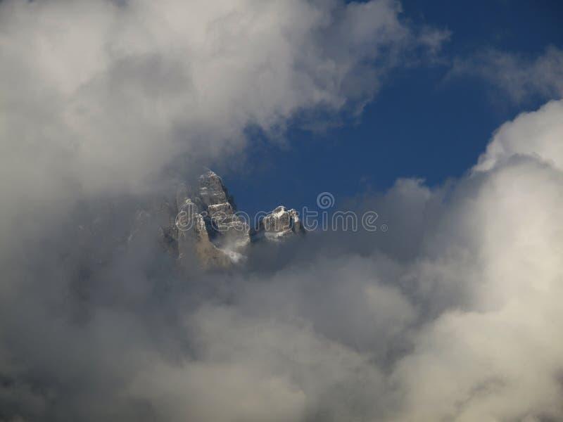 在雾山峰的石峰在雾云彩后的天空蔚蓝皮下 免版税库存图片