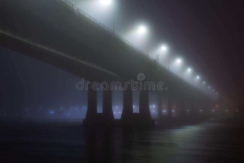 在雾或薄雾的桥梁在夜之前 免版税库存图片