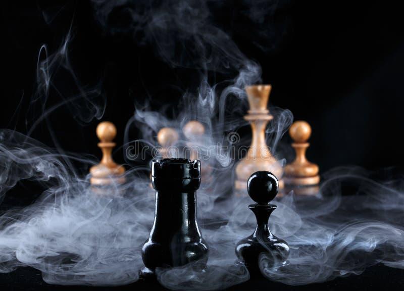 在雾的两个黑棋子在白色图对面 免版税库存照片