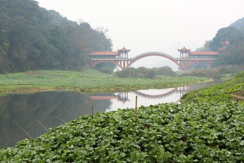 在雾的古老传统红色桥梁在乐山-中国 免版税库存图片