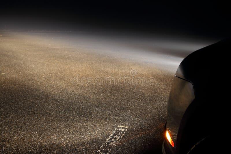 在雾的汽车车灯 免版税库存照片