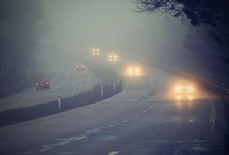 在雾的汽车 坏冬天天气和危险交通在路 在雾的轻型车辆 库存照片