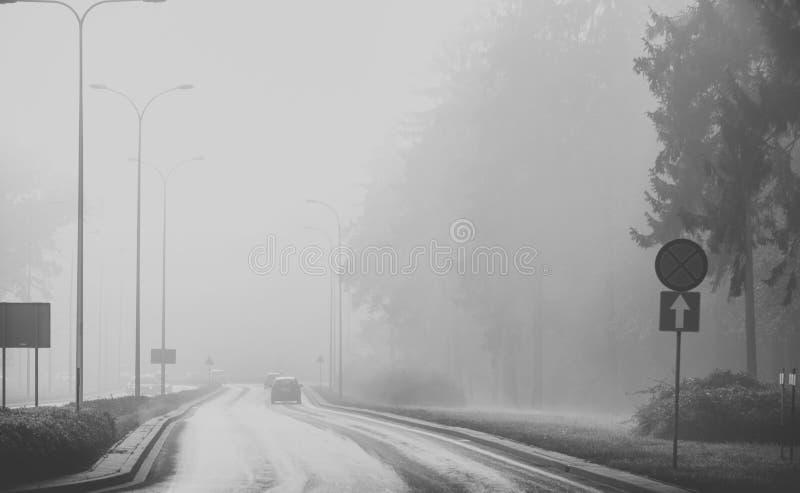 在雾的汽车 恶劣天气和危险交通在路 黑色白色 库存照片