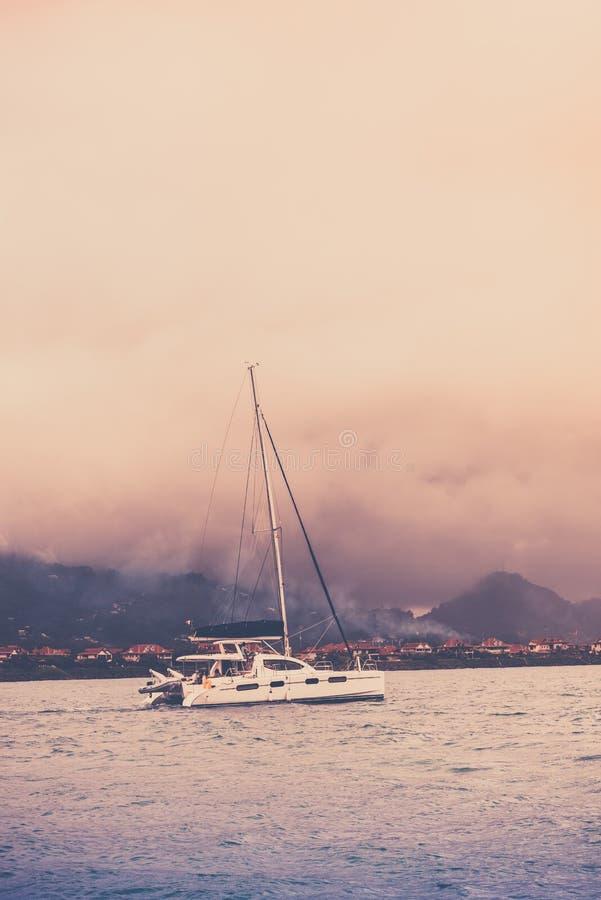 在雾的消遣游艇在塞舌尔群岛的海岸 免版税图库摄影