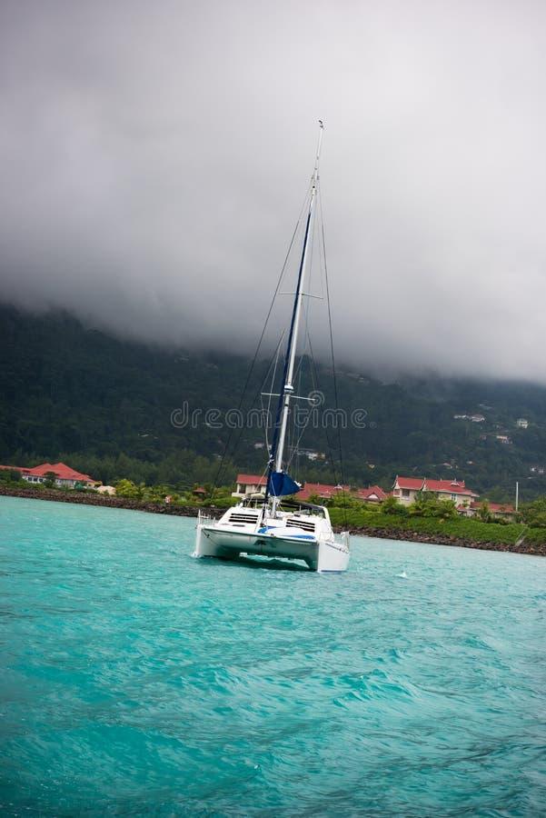 在雾的消遣游艇在塞舌尔群岛的海岸 免版税库存照片