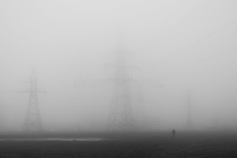在雾的电送电线 免版税库存图片