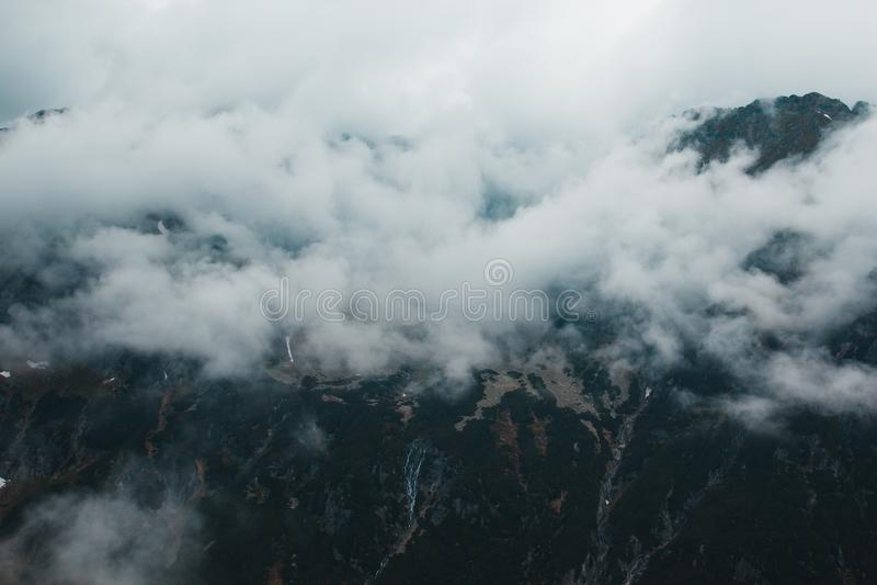 在雾的美好的黑暗的喜怒无常的可怕山风景 免版税图库摄影