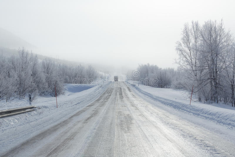 在雾的遥远的结冰的路在冬天 免版税图库摄影