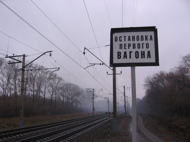 在雾的铁路路轨与标志中止在驻地的第一辆汽车 免版税库存照片