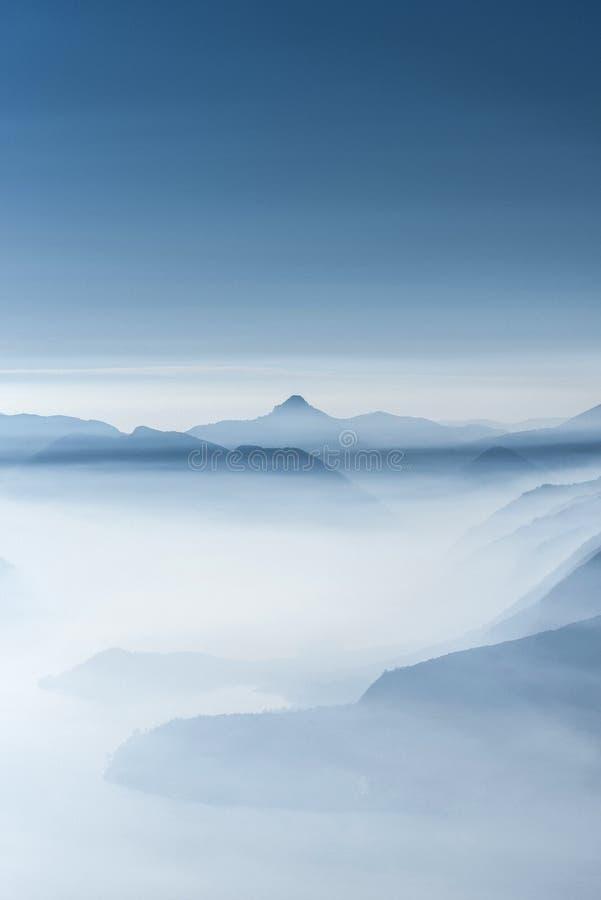 在雾盖的高白色小山顶和山美丽的射击  图库摄影