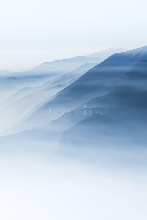 在雾盖的高白色小山顶和山美丽的射击  免版税库存照片