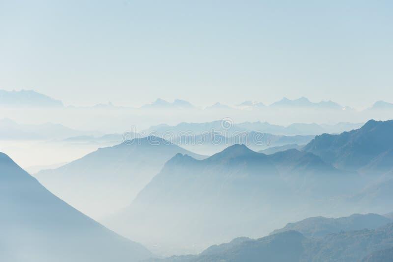 在雾盖的高白色小山顶和山美丽的射击  免版税图库摄影