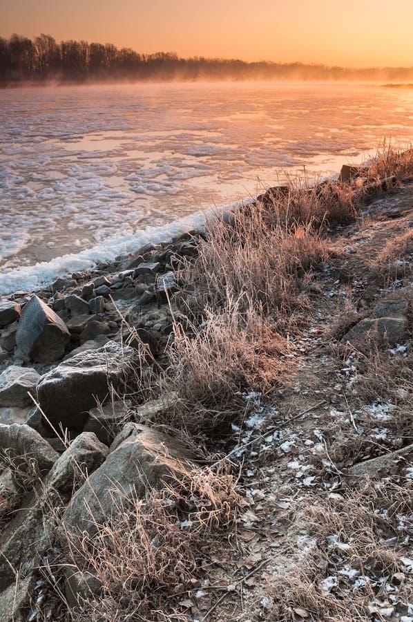 在雾盖的结冰的河一石河岸的日出 免版税图库摄影