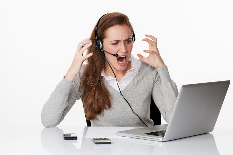 在震动下的恼怒的20s职业妇女与耳机和计算机 免版税库存图片