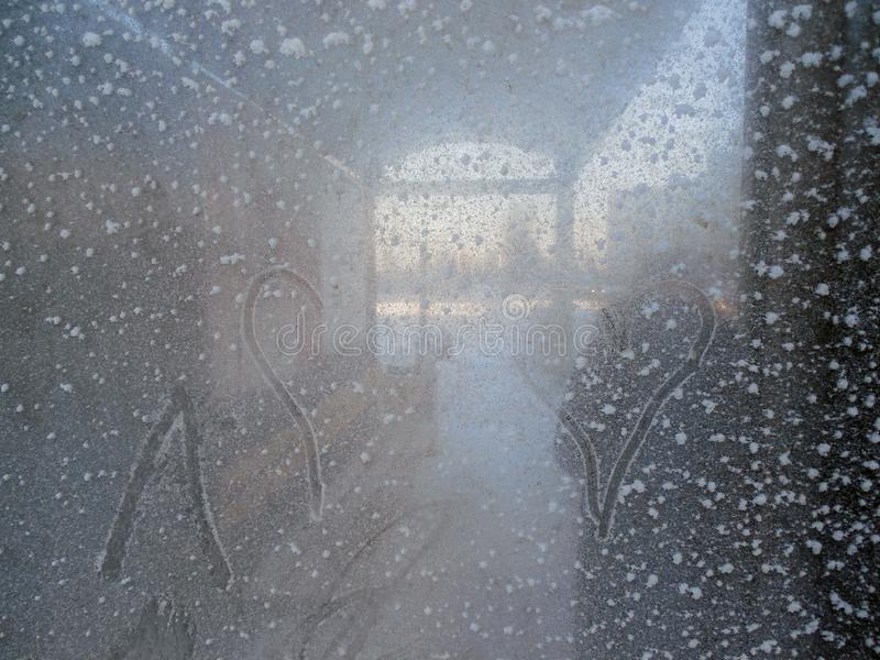 在霜的玻璃窗在冬天和与心脏样式 库存照片