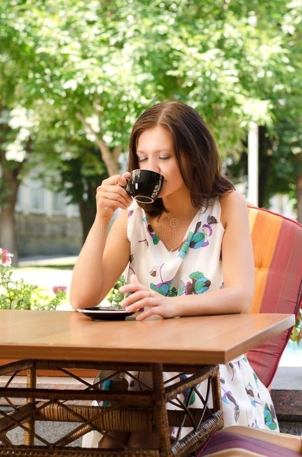 在露天咖啡馆的妇女饮用的咖啡 免版税库存图片