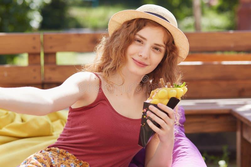 在露天坐frameless椅子,吃冰淇淋和拍selfie照片的年轻女人画象在夏天公园,放松 免版税库存照片