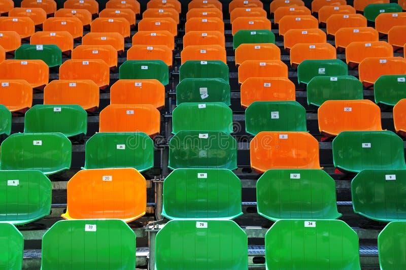 在露天正面看台的被编号的塑料位子 免版税库存照片