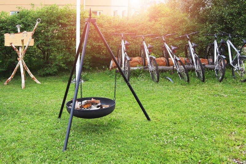 在露营地的壁炉 小组frineds停放的自行车临近树 户外旅行和体育活动 图库摄影