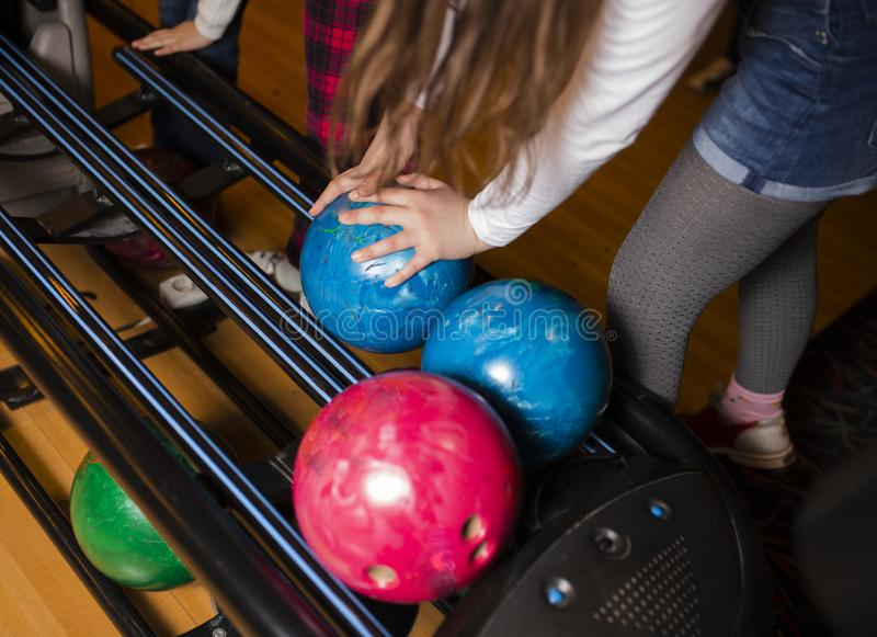 在青少年的儿童手藏品保龄球的特写镜头反对保龄球场-图象 快乐的孩子准备演奏-图象 的treadled 免版税图库摄影