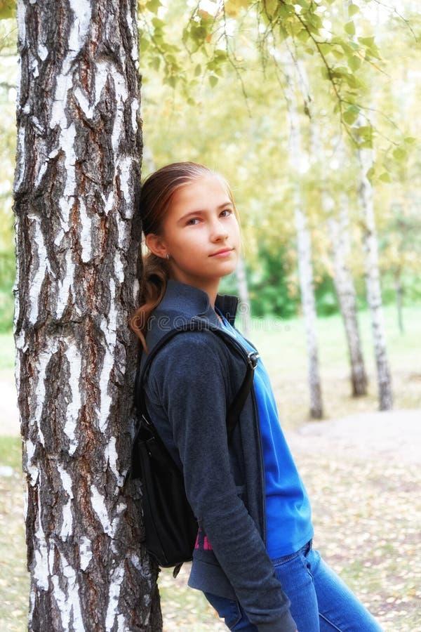 在青少年的女孩的浪漫心情在秋天桦树树丛里 精美桃红色花开了花在迷离背景的日本樱桃树 库存照片