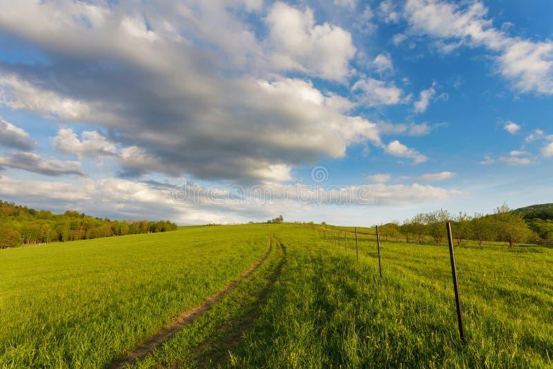在青山和乡下公路的蓝色多云天空 免版税库存图片