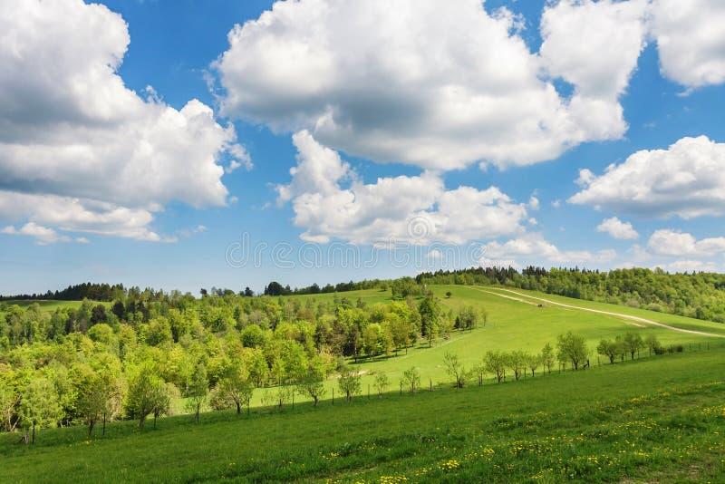 在青山和乡下公路的蓝色多云天空 免版税库存照片