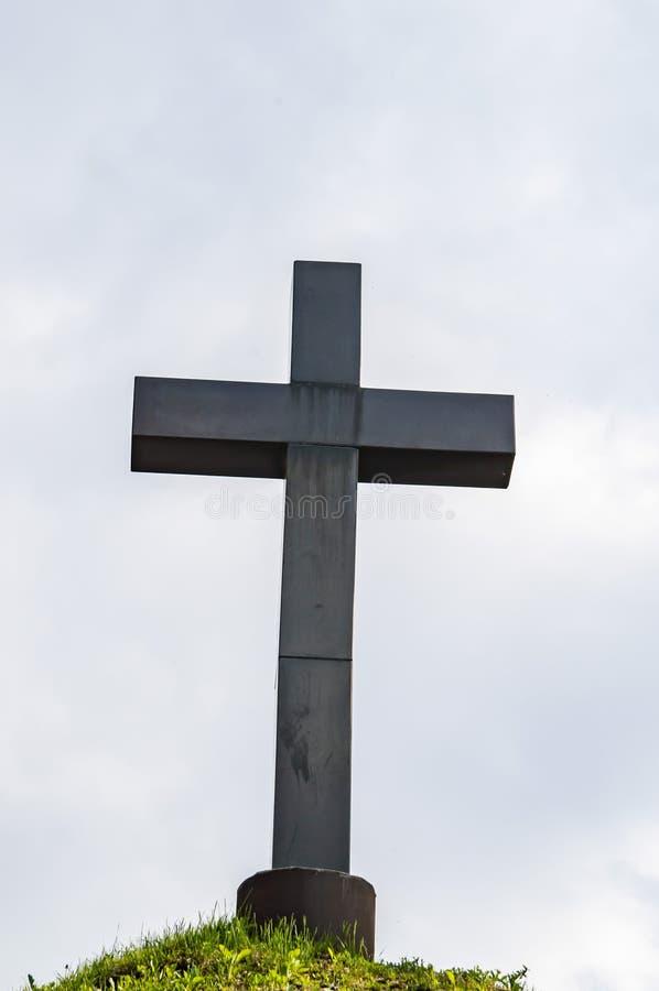 在青山小山的基督徒十字架在多云天空下 免版税库存照片