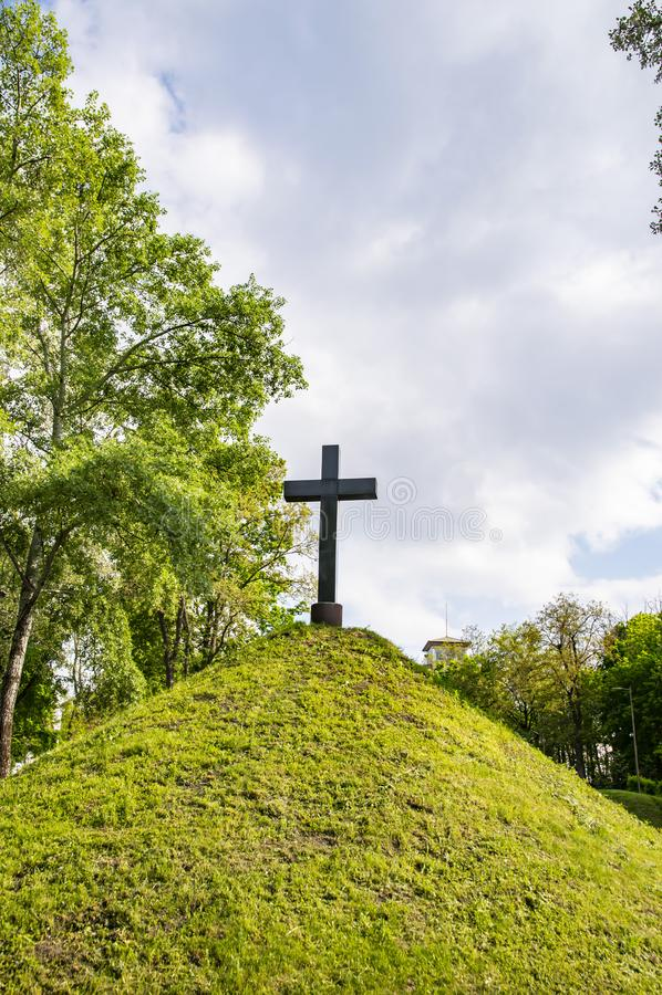 在青山小山的基督徒十字架在多云天空下 库存照片