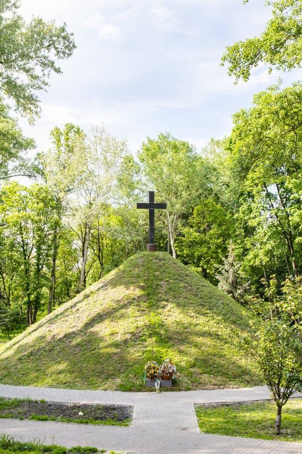 在青山小山的基督徒十字架在多云天空下 免版税库存图片