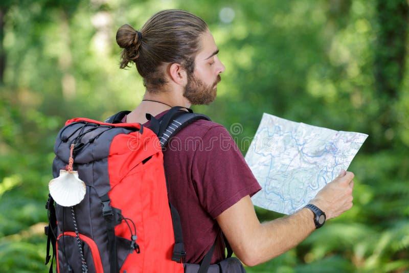 在青山附近的男性徒步旅行者读书地图 免版税图库摄影