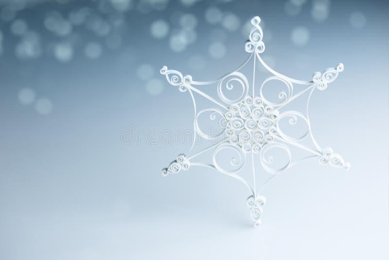 在青水平的美丽的白色手工制造quilling的雪花 库存照片