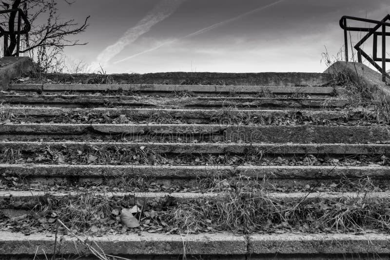 在非常不良状态的老台阶与在一家被放弃的工厂附近的秋叶 免版税库存照片