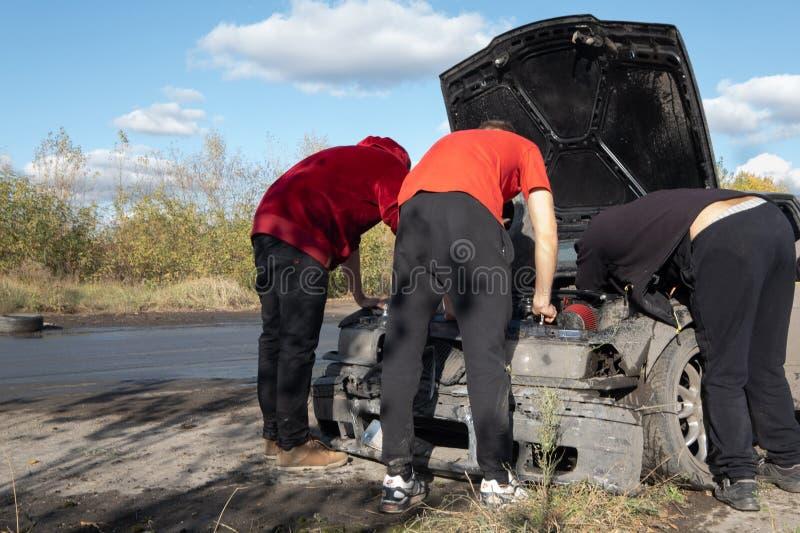 在非职业漂移的事件期间,3个人修理损坏的汽车 库存照片