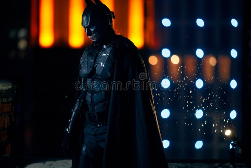 在面具、装甲和斗篷立场打扮的一个人以夜城市光为背景 库存图片