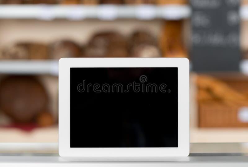 在面包店商店柜台的数字式片剂 免版税库存图片