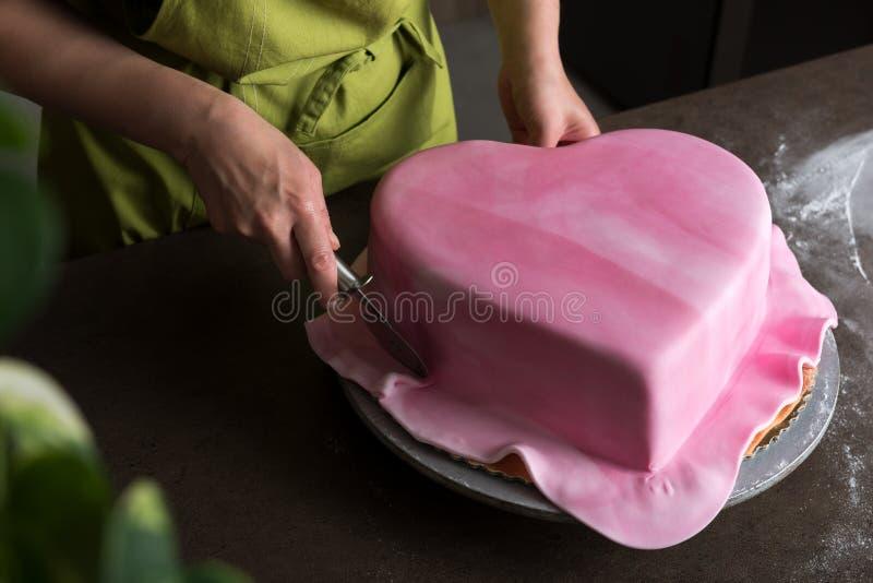 在面包店从上面装饰与桃红色方旦糖,看法的妇女心形的婚宴喜饼 库存图片