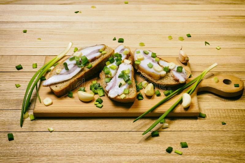 在面包片的Salo用大蒜和葱在一个木切板 免版税图库摄影