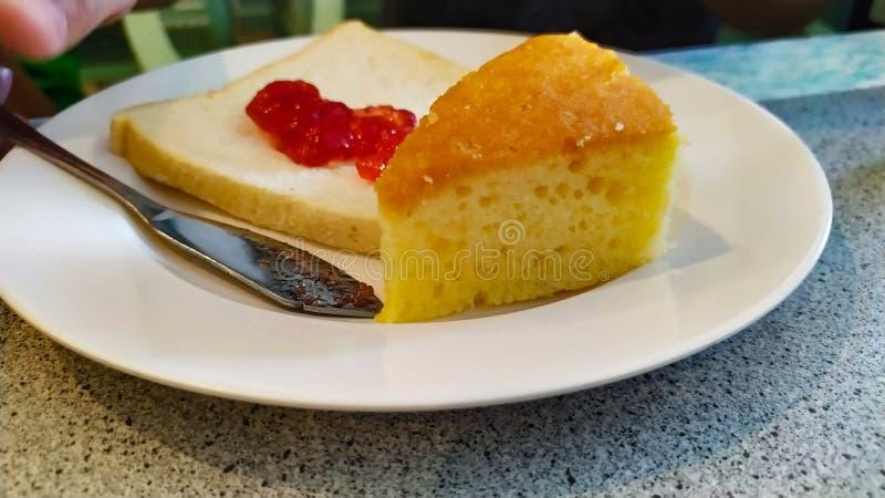 在面包的蛋糕和草莓酱在非常可口盘的白色 免版税库存照片