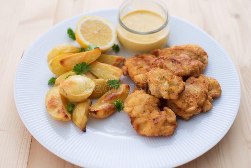 在面团或鳕鱼油炸馅饼的鳕鱼服务用与荷兰芹叶子的被烘烤的土豆,并且家做了蛋黄酱调味汁 库存图片
